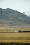 Casa fuori città, montagna rocciosa, campo asciutto, Islanda Immagini Stock Libere da Diritti