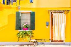Casa gialla con i fiori e le piante Case variopinte nell'isola di Burano vicino a Venezia, Italia Fotografia Stock