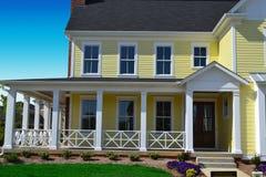 Casa gialla di stile della Nuova Inghilterra con il portico Fotografia Stock Libera da Diritti
