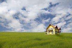 Casa gialla sul campo di erba Immagine Stock