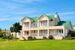 Casa grande agradable, césped, banco imagen de archivo libre de regalías