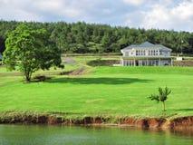 Casa grande com gramado ao lado do lago fotos de stock royalty free