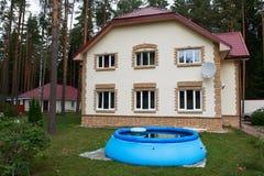 Casa grande fuera de la ciudad y de una piscina inflable Fotos de archivo libres de regalías