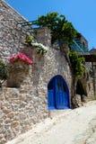 Casa griega con la puerta y las flores azules Fotos de archivo