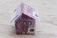 Casa hecha de billetes de banco euro en un fondo de madera fotos de archivo