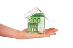 Casa hecha de cuentas euro en la mano de la hembra fotografía de archivo