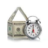 Casa hecha de dólares y del reloj de alarma. Imagen de archivo libre de regalías