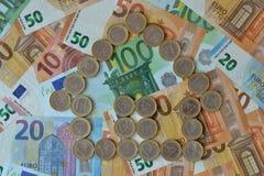 Casa hecha de monedas euro en el fondo euro de los billetes de banco - concepto de negocio de las propiedades inmobiliarias fotos de archivo