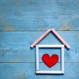 Casa hecha de tiza con el corazón rojo en él en backgrou de madera azul fotografía de archivo