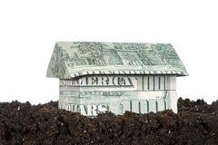 Casa hecha del dinero en la tierra Imagenes de archivo