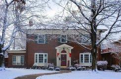 Casa hermosa del ladrillo con las ventanas saledizas con el árbol de navidad que muestra pilares y el trineo directos y adornados imágenes de archivo libres de regalías