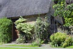 Casa inglesa de piedra con la flor, arbusto, jardín del árbol Foto de archivo libre de regalías