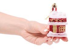 Casa innevata della decorazione di Natale su un albero a disposizione Immagine Stock
