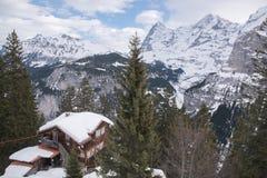 Casa innevata di cliffside e della catena montuosa a Murren, Svizzera, Europa Immagine Stock