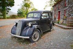 Casa irlandesa de la cabaña con el coche del vintage Foto de archivo