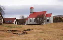 Casa islandêsa tradicional com suportes vermelhos do telhado nos montes de uma grama seca amarela no fundo do céu foto de stock