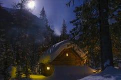 Casa leggiadramente, il fumo dal camino, notte illuminata dalla luna di inverno Immagine Stock Libera da Diritti