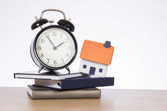 Casa, libros y concepto de la hipoteca del reloj que hace tictac Fotografía de archivo libre de regalías