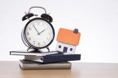 Casa, livros e conceito de tiquetaque da hipoteca do pulso de disparo Fotografia de Stock Royalty Free
