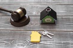Casa, llaves de la casa con un llavero, martillo del juez en un fondo de madera imagenes de archivo