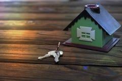 Casa, llaves en una tabla de madera Foto de archivo libre de regalías