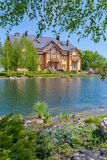 Casa lujosa en la orilla de un lago limpio con los abedules alrededor Viva en un regalo tan continuo Imágenes de archivo libres de regalías