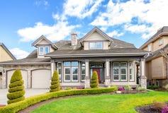 Casa luxuosa com ajardinar bonito em um dia ensolarado Imagem de Stock Royalty Free