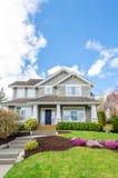 Casa luxuosa com ajardinar bonito em um dia ensolarado Imagens de Stock Royalty Free