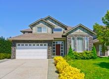 Casa luxuosa da família com fundo da entrada de automóveis concreta e do céu azul Fotos de Stock Royalty Free