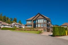 Casa luxuosa na vizinhança no fundo do céu azul Fotos de Stock