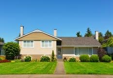 Casa média da família com gramado verde e árvores na parte dianteira no fundo do céu azul fotografia de stock