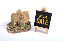 Casa miniatura con per il fondo di bianco del segno di vendita Fotografia Stock Libera da Diritti