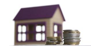 Casa miniatura con un mucchio delle monete di tema Fotografia Stock Libera da Diritti