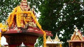 Casa miniatura de madera del alcohol de guarda Peque?a capilla del templo budista, guirnaldas coloridas de la flor Phum del phra  almacen de video