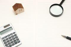 Casa miniatura, lente d'ingrandimento, calcolatore sul taccuino in bianco immagine stock libera da diritti