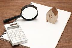 Casa miniatura, lupa, calculadora en el cuaderno en blanco Imagen de archivo libre de regalías