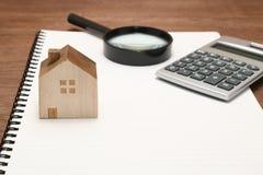 Casa miniatura, lupa, calculadora en el cuaderno en blanco Fotos de archivo
