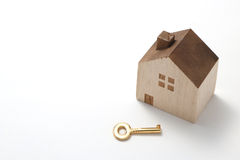 Casa miniatura y llave aisladas en el fondo blanco Imagenes de archivo