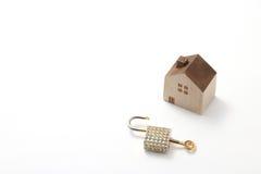 Casa miniatura y llave aisladas en el fondo blanco Imagen de archivo