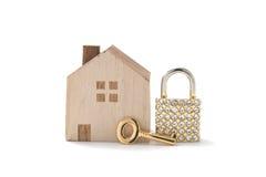 Casa miniatura y llave en el fondo blanco Foto de archivo