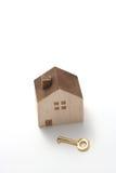 Casa miniatura y llave en el fondo blanco Foto de archivo libre de regalías