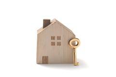 Casa miniatura y llave en el fondo blanco Fotos de archivo