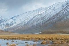 Casa minuscola, montagna enorme e stagno nel foregruond Fotografie Stock Libere da Diritti