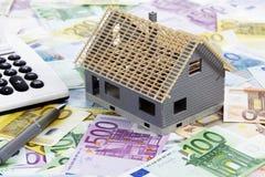 Casa modelo com calculadora e pena no montão de euro- notas Foto de Stock