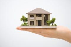 Casa modelo com uma mão Fotografia de Stock Royalty Free