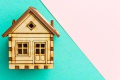Casa modelo de madeira em um rosa geométrico e em um fundo pastel de turquesa com espaço da cópia Teste padrão, formulário Casa d Foto de Stock