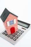 Casa modelo que se reclina sobre la calculadora Imagen de archivo