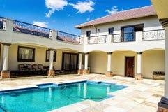 Casa moderna con el cielo azul y la hierba verde con una fuente de agua Fotografía de archivo libre de regalías