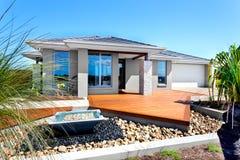 Casa moderna con gli alberi e gli elementi di pietra della decorazione compreso una s Fotografia Stock Libera da Diritti