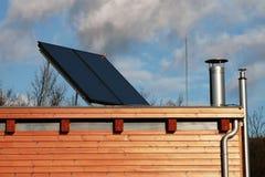 Casa moderna con i comitati solari sul tetto per il riscaldamento dell'acqua Fotografia Stock Libera da Diritti